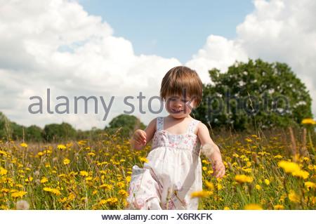 Une petite fille qui marche dans une prairie de fleurs sauvages Banque D'Images
