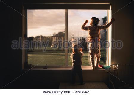 Garçon et fille s'appuyant sur la fenêtre dans la condensation du matin Banque D'Images