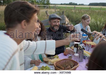 Les amis de boire du vin rouge et manger, profiter dîner garden party Banque D'Images