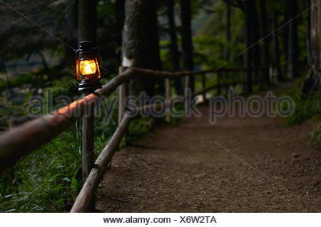 Lampe à huile allumé sur clôture le long chemin forestiers Banque D'Images