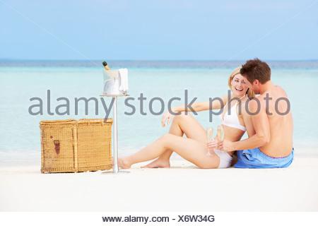 Couple sur la plage avec pique-nique Champagne De Luxe Banque D'Images