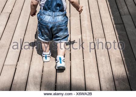 Bébé garçon apprendre à marcher par lui-même. Il apprend à surmonter les obstacles et les nouvelles la surface au sol.