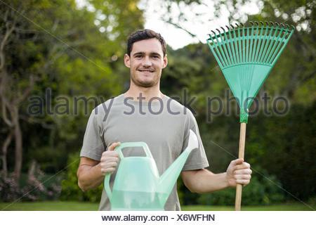 Portrait de jeune homme debout avec un râteau de jardinage et d'arrosoir Banque D'Images