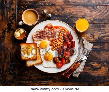Le petit déjeuner anglais complet avec les œufs, saucisses, bacon, haricots, des toasts et du café sur fond de bois Banque D'Images