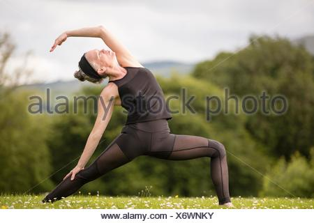 Young woman standing in field Banque D'Images
