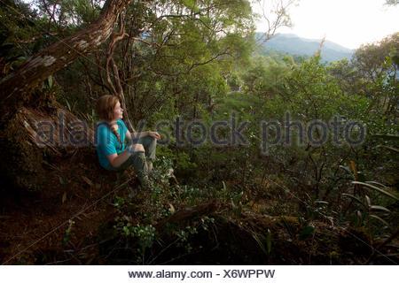Une fille regarde le lever du soleil à partir de la roche moussue, un point élevé sur la crête à Gunung Palung National Park. Banque D'Images