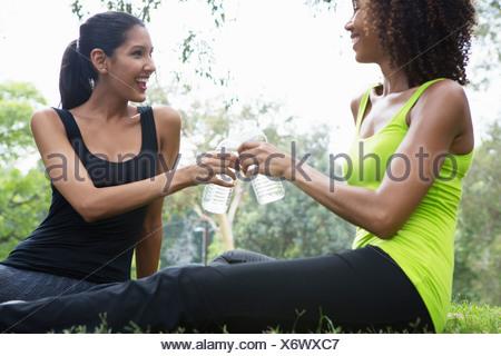 Young et jeune femme avec dégustation de bouteilles d'eau dans park Banque D'Images