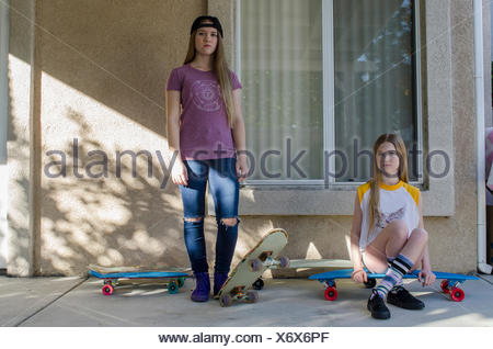 Portrait de deux jeunes sœurs skateboarder on porch Banque D'Images