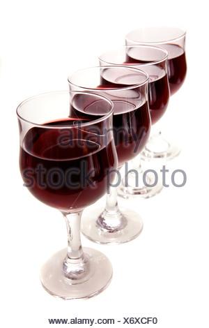 Quatre verres de vin rouge,la queue à un angle,isolé sur blanc. Banque D'Images