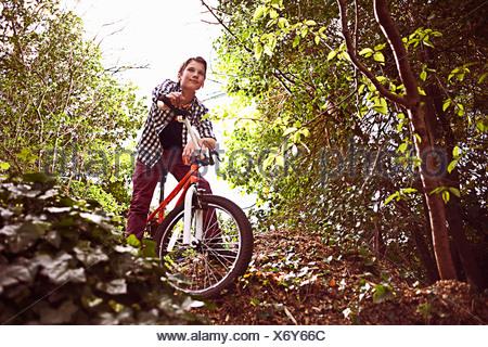 Vélo garçon à travers la forêt Banque D'Images