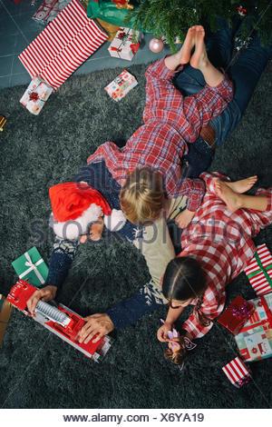 Père couché sur salon-de-chaussée de l'ouverture des cadeaux de Noël avec ma fille et fils Banque D'Images