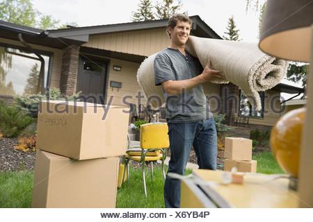 Homme portant un tapis parmi les effets personnels dans la cour avant Banque D'Images