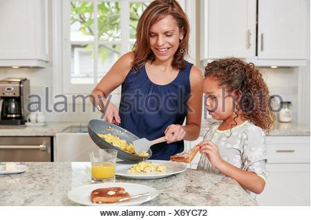 Mère au comptoir de la cuisine servant fille œufs brouillés de poêle Banque D'Images