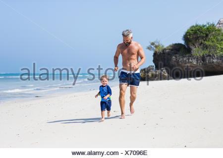 Père et fils s'exécutant sur la plage de Diani, Kenya Banque D'Images