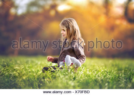 Girl sitting in a field in soft toy Banque D'Images