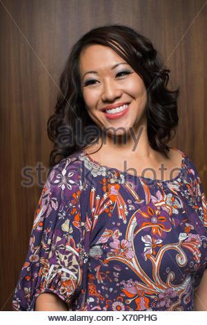 Portrait of smiling brunette woman wearing blouse à motifs Banque D'Images