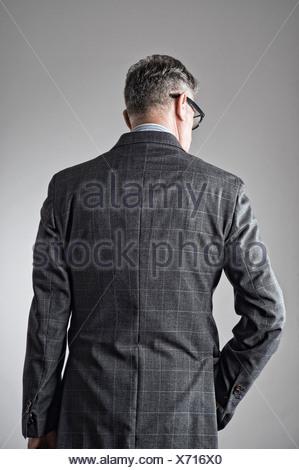 Portrait of senior man, portant costume, vue arrière Banque D'Images