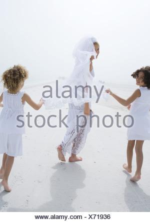 Mariée et les filles fleurs running on beach Banque D'Images