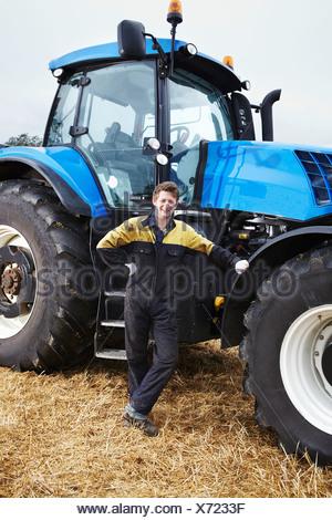 Farmer standing par le tracteur dans le champ, Banque D'Images
