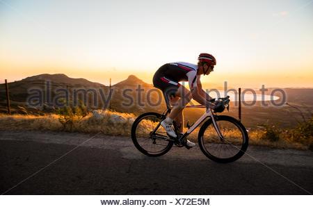 Homme randonnée à vélo au coucher du soleil, Corse, France Banque D'Images