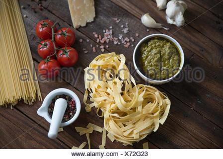 Les pâtes, le pesto, l'ail, les tomates et le parmesan sur la table Banque D'Images