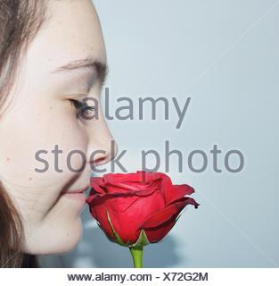 Close-up portrait of a woman with eyes closed smelling a fleur rose Banque D'Images