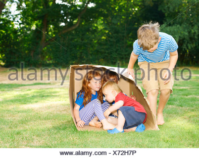 Frères et sœurs hiding in cardboard box in garden Banque D'Images