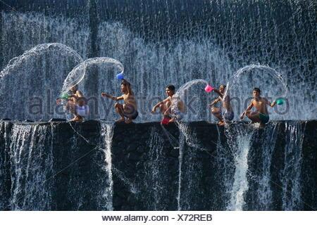 Cinq enfants aux projections d'eau, barrage Unda Tukad, Bali, Indonésie Banque D'Images