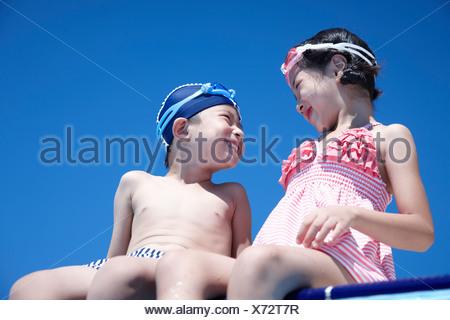 Garçon et fille assise sur le bord de la piscine à l'affiche Banque D'Images