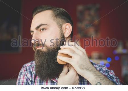 Jeune homme barbu, sa barbe de brossage Banque D'Images