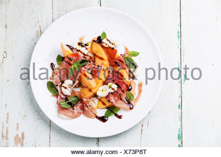 Melon et jambon prosciutto salade avec de la mozzarella et de feuilles de menthe Banque D'Images