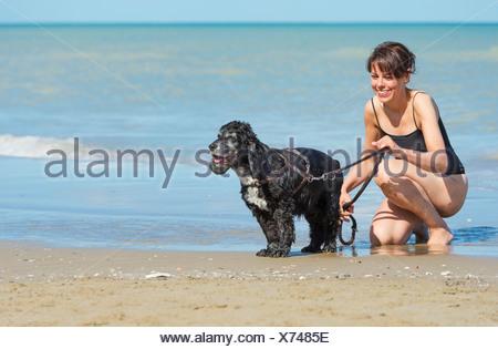 Une femme avec son chien à la plage; Rimini, Émilie-Romagne, Italie Banque D'Images