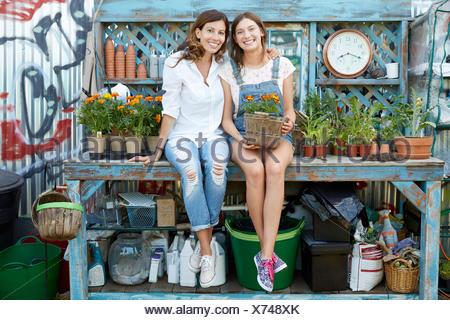 Portrait smiling Latina mère et fille adolescente planter des fleurs à table de jardin Banque D'Images