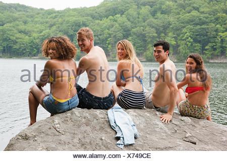 Portrait friends sitting on rock lakeside Banque D'Images