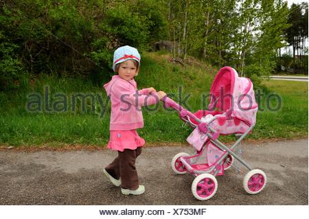 Vue de côté portrait d'une petite fille avec la pram de poupée Banque D'Images