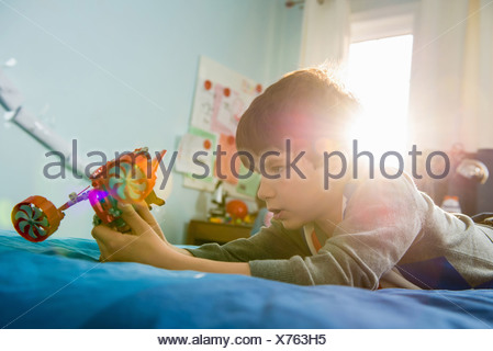 Boy lying on bed with toy Banque D'Images