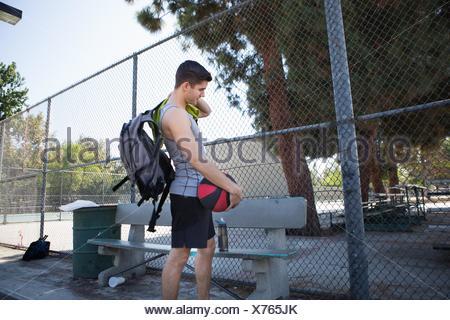 Jeune joueur de basket-ball masculin s'apprête à quitter la cour de basket-ball Banque D'Images