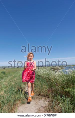 Fille qui marche par river marsh Banque D'Images
