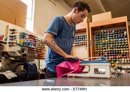 Machine à broder à l'aide de travailleurs dans l'atelier d'impression t-shirt Banque D'Images