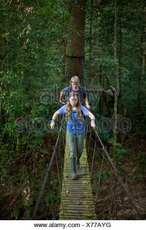Un garçon et fille traverser un pont suspendu dans la forêt pluviale de Bornéo. Banque D'Images
