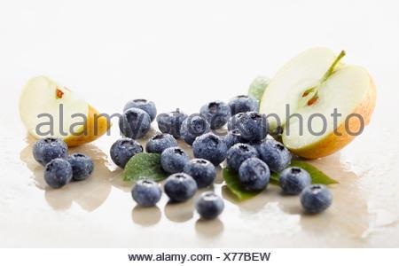 Myrtille, Vaccinium corymbosum cultivar. Plusieurs des petits fruits avec demi et quart de pomme et spritzed avec de l'eau organisé sur le marbre blanc. Focus sélectif. Banque D'Images