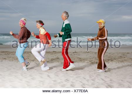 Quatre cadres supérieurs des profils d'exécution sur la plage Banque D'Images