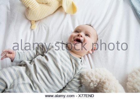 Laughing baby laying on bed Banque D'Images