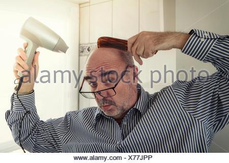 Homme chauve avec un peigne et d'un sèche-cheveux coiffure, Allemagne Banque D'Images