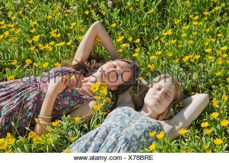 Les jeunes filles portant dans le champ de fleurs Banque D'Images