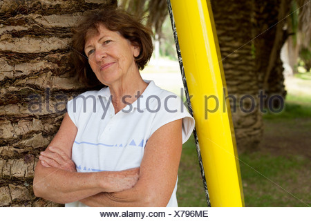 Portrait of senior woman leaning against palm tree in park Banque D'Images