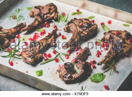 Côtes d'agneau grillées avec graines de grenade, de la menthe et romarin en metal la lèchefrite, selective focus, composition horizontale. Barbecue de viande et slo Banque D'Images