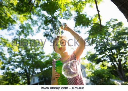 Une jeune fille faisant des bulles dans l'air sous les branches d'un gros arbre. Banque D'Images
