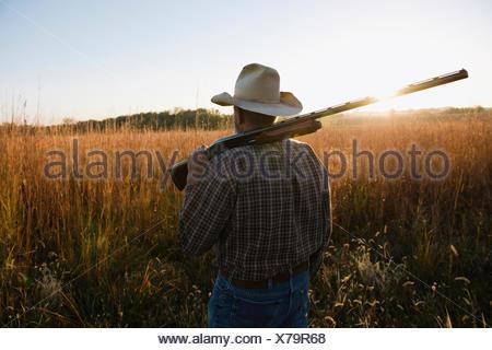 Producteur senior avec fusil sur l'épaule dans les zones reculées au crépuscule, Plattsburg, New York, USA Banque D'Images