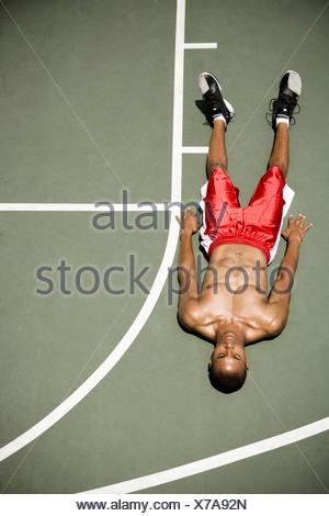 L'homme portant sur un terrain de basket-ball extérieur Banque D'Images